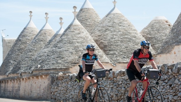 Pedalling past the iconic trulli of Puglia - ancient pointy-roofed, conical-shaped stone huts dotted in and around ...