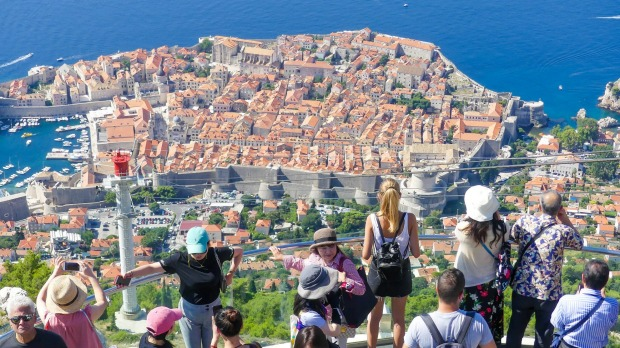 Tourists looking out over panorama view of old town Dubrovnik.