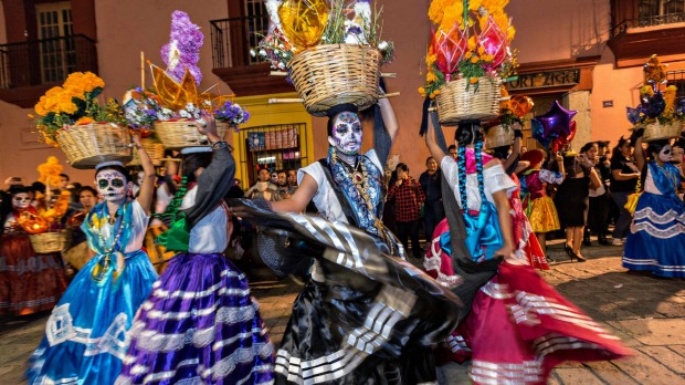 Costumed dancers at a Comparsa, or parade, during the Day of the Dead festival.
