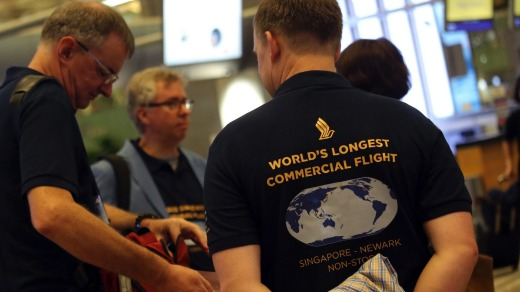 Passengers with their own self-designed T-shirts to celebrate the flight wait at the check-in counter at Changi Airport.