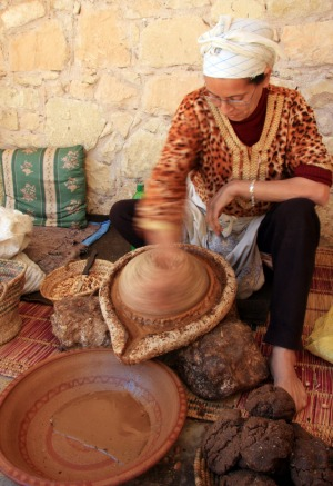 Berber woman extracting oil from Argan nut kernals at the Assous Argane oil co-operative, Souss Valley, Morocco.