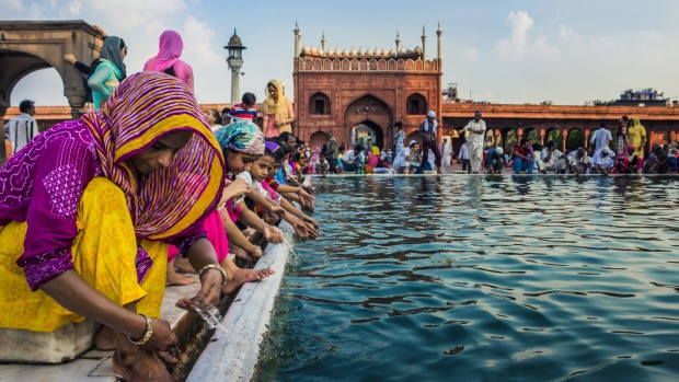 People wash themselves with water from an artificial pond at the premises of Jama Masjid, Delhi.