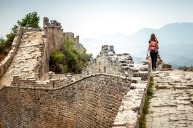 Solo Woman Tourist at walking on the Great Wall Of China. She is wearing a backpack. sunnov11cover New Year New You ; ...