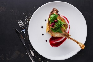 Exclusive restaurant meals. Duck confit with braised cabbage, baked apple and cranberry sauce served on snow white plate ...