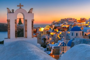 Arch with a bell, white houses and church with blue domes in Oia or Ia at golden sunset, island Santorini, Greece.