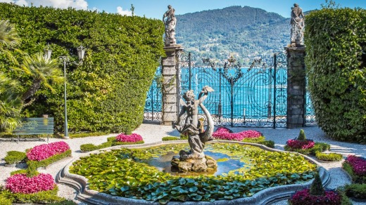 Old fountain with stone statue in beautiful garden, villa Carlotta, Como lake, Italy.