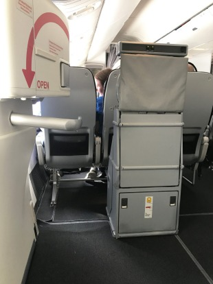 The space in front of row 26, Economy X seats, either side of the plane.