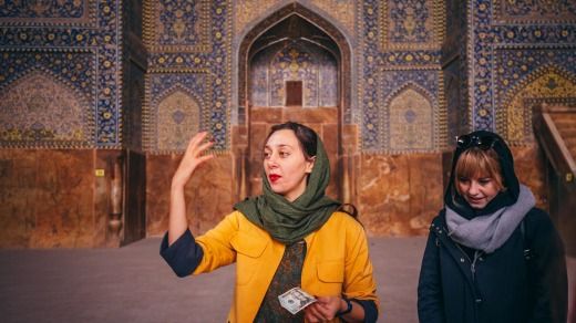 Intrepid local leader Nadia Badiee uses a dollar bill to demonstrate the strange acoustics inside Shah Mosque, Esfahan.
