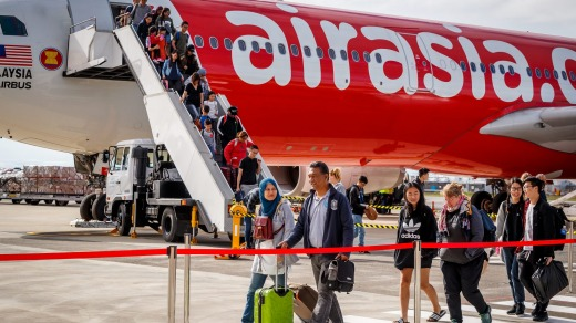 Passengers walks across the tarmac after arriving on AirAsia X's inaugural flight to Avalon from Kuala Lumpur.