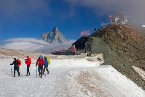 The Matterhorn rises above the clouds, a group of hikers and Rifugio Teodulo.