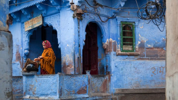 Indian woman standing on her terrace in Jodhpur, India's Blue city.