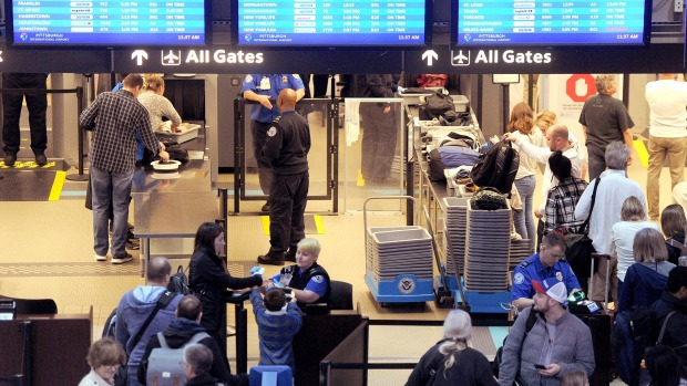 Transportation Security Administration security officers check passengers through security at the Pittsburgh ...