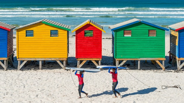 Smiling surfers walking by the beach cabins and huts of Muizenberg, a famous surfing spot near Cape Town.