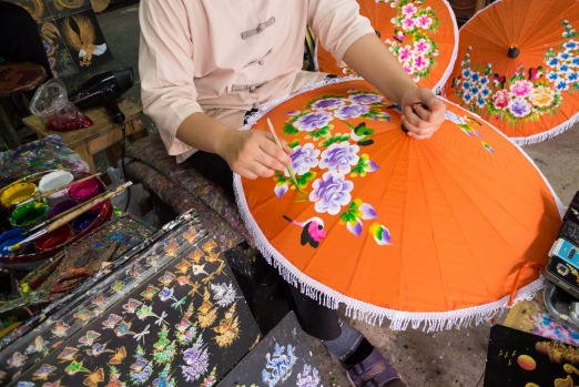 PARASOL PAINTING: Beautifully-painted umbrellas and parasols are synonymous with Chiang Mai and particularly the village ...