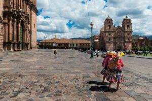 Two women wearing traditional clothes walking in the Plaza de Armas, in Cusco.