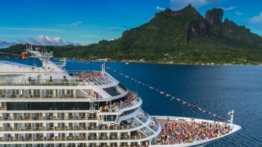 Crew and guests at the bow of the Viking Sun near Bora-Bora, French Polynesia.