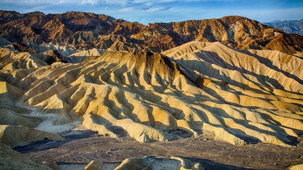 The sun rises over Zabriskie Point in Death Valley National Park, California.