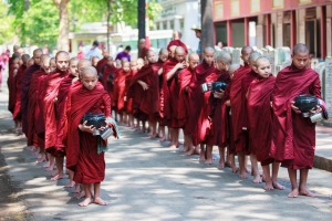 Young buddhist novices walk to collect alms and offerings in the monastery of Maha Gandhayon Kyaung.