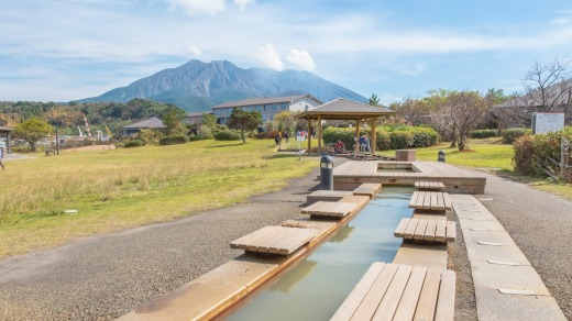 Sakurajima overlooks a foot onsen.