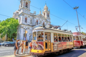 The historic Tram 28 in front of baroque and neoclassical Estrela Basilica in Lisbon.