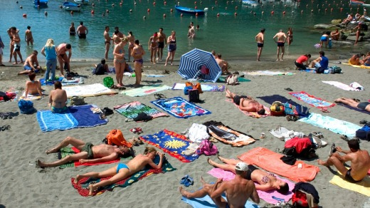 Tourists relax on a beach in the Cinque Terre.
