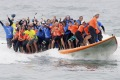 Sixty-six surfers from around the world ride a custom built surfboard for 12 seconds to break the world record.