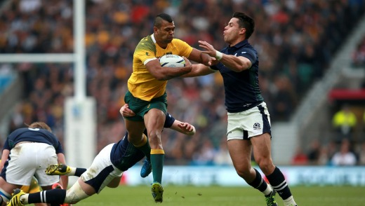 Australia's Kurtley Beale (centre) evades the challenges of Scotland's Finn Russell (left) and Sean Maitland during the ...
