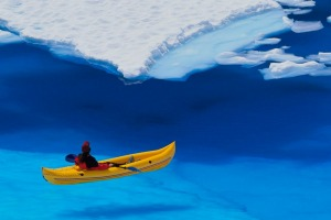 A kayaker navigates through a melt pond in the Juneau Icefield, Coast Mountains, Tongass National Forest.