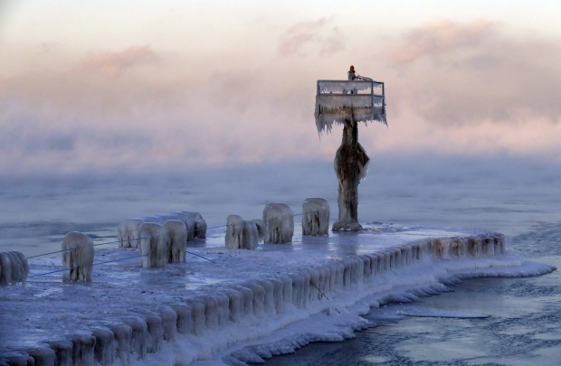 A harbour light is covered by snow and ice on Lake Michigan.