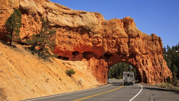 A truck-camper passes through a small tunnel along Highway 12 Scenic Byway in Red Canyon, Utah. Highway 12 runs from its ...