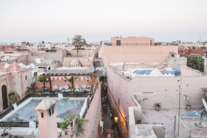 Pink-hued buildings stand among narrow alleyways in Marrakech.