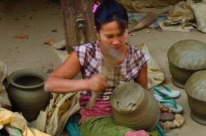 A woman beats clay waterpots into shape with  a wooden paddle at Yandabo village  near Mandalay.