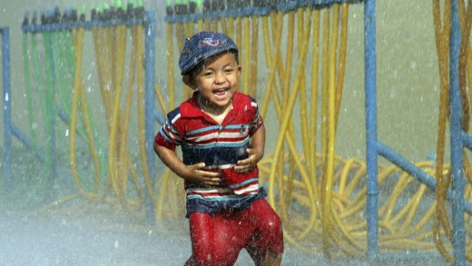 A little boy is splashed with water during the opening ceremony of the annual Thingyan water festival celebrations in Yangon.