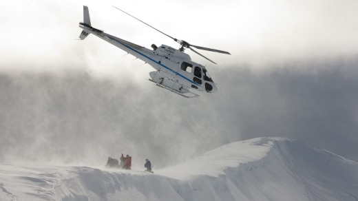 Skiers are dropped off on a ridge by helicopter.