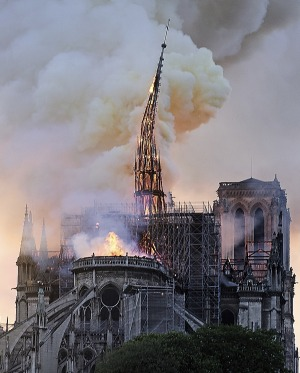 Flames and smoke rise as the spire on Notre Dame cathedral collapses in Paris, Monday, April 15, 2019. Massive plumes of ...