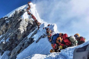 Climbers line up to stand at the summit of Mount Everest.