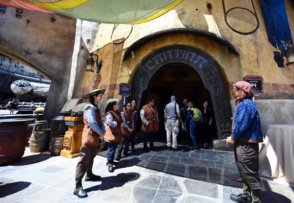 The outside of Oga's Cantina is lined with greeters in costume.