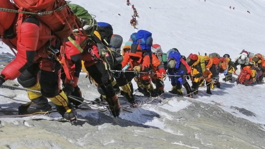 A long queue of mountain climbers line a path on Mount Everest just below camp four.