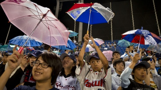 Fans of the Yakult Swallows Japan League baseball team sing and hold umbrellas overhead when one of their team's players ...