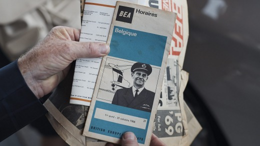 Frank Dell examines a vintage British Airways flight schedule, featuring an image of himself.