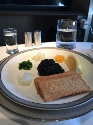Caviar served with a side of vodka, neat, in First.