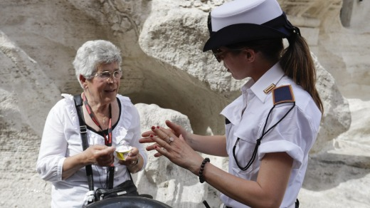 A city police officer talks to a woman having an ice-cream by the Trevi fountain. City authorities are cracking down on ...