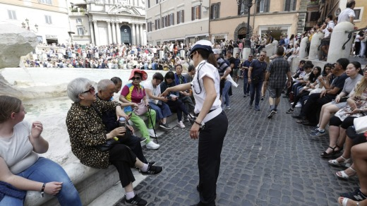 A police officer talks to tourists gathered in front of Trevi fountain.