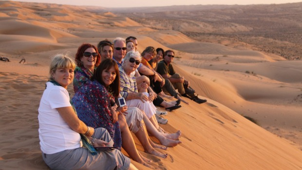 A Peregrine Adventures group enjoys the view from atop a dune.