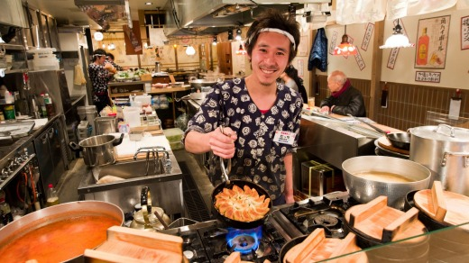 A chef cooking gyoza in a traditional restaurant, Japan.