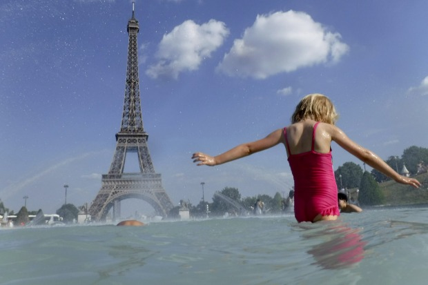 A girl cools off in the fountain of the Trocadero in front of the Eiffel Tower.