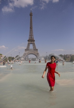 A woman cools off in the fountain of Trocadero, in Paris.