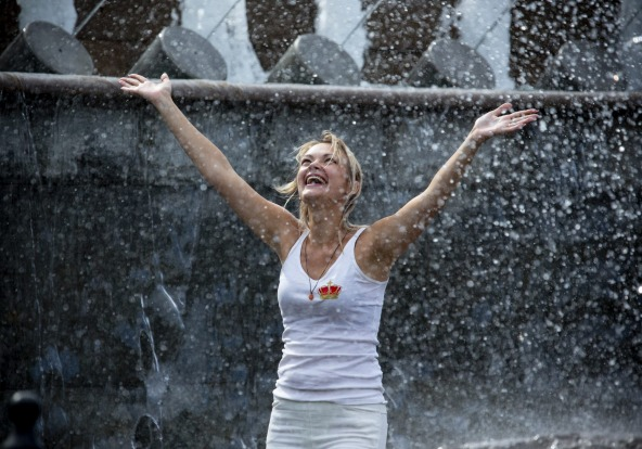 A woman cools off in a fountain in Alexander Garden near the Kremlin Wall in Moscow, Russia.