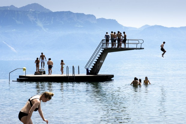 Children jump into the water of Lake Geneva play to cool off during the sunny and warm weather, in Lutry, Switzerland.