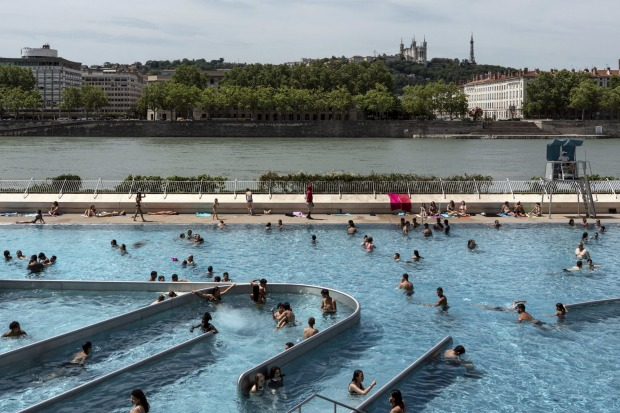 People visit a swimming pool in the center of Lyon, central France.